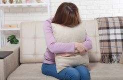 Piękna w średnim wieku brunetki kobieta trzyma poduszkę i płacze na kanapie Domowy tło Przekwitanie czas obraz royalty free