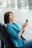 Piękna w średnim wieku kobieta patrzeje telefon komórkowego Obrazy Stock