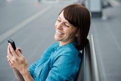 Piękna w średnim wieku kobieta patrzeje telefon komórkowego Fotografia Royalty Free