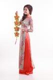 Piękna Wietnamska kobieta jest ubranym wrażenie ao Dai trzyma szczęsliwym dekoruje przedmiot Fotografia Stock