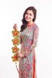 Piękna Wietnamska kobieta jest ubranym wrażenie ao Dai trzyma szczęsliwym dekoruje przedmiot Zdjęcia Royalty Free