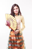 Piękna Wietnamska młoda kobieta z nowożytnym stylem ao Dai trzyma papierowego fan Zdjęcie Royalty Free