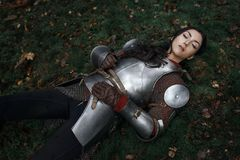Piękna wojownik dziewczyna jest ubranym chainmail i opancerzenia lying on the beach na ziemi w tajemniczym lesie zdjęcie royalty free