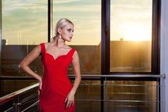 Piękna wspaniała blondynki dziewczyna w czerwonej sukni pozuje blisko szklanej gabloty wystawowej w centrum biznesu Słoneczny rac Fotografia Royalty Free