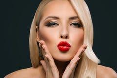 piękna wspaniała kobieta z makeup i fryzury dmuchaniem całuje, zdjęcia royalty free