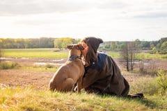 Piękna wycieczkuje dziewczyna siedzi na wzgórza i buziaka zwierzęcia domowego psie przy spacerem obrazy stock