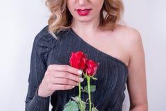 Piękna wzorcowa kobieta trzyma dwa czerwonej róży obraz stock