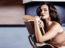 Piękna Yong brunetki kobieta siedzi blisko graby w domu, zima ciepły wieczór w wnętrzu obraz stock
