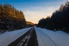 Piękna zimy droga przez śnieżnych poly, zmierzchu i lasów, Obraz Royalty Free