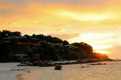 Piękna zmierzch plaża i łódkowaty pobliski halny kurort Fotografia Royalty Free