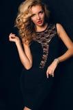 Piękna zmysłowa kobieta z blond kędzierzawym włosy w eleganckiej czerni koronki sukni Zdjęcia Royalty Free