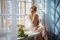 Piękna zmysłowa młoda blond kobieta w beżowej sukni siedzi na a zdjęcia royalty free