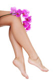 Piękne żeńskie nogi i storczykowy kwiat Obraz Stock