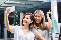 Piękne azjatykcie dziewczyny trzyma torba na zakupy, używa mądrze telefonu selfie i ono uśmiecha się, podczas gdy stojący outdoor obrazy royalty free
