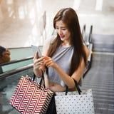 Piękne azjatykcie dziewczyny z torba na zakupy używać smartphone Fotografia Royalty Free