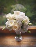Piękne białe róże w szklanym wazowym pobliskim okno Fotografia Stock