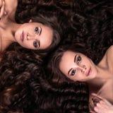 Piękne bliźniak młode kobiety z naturalnego makijażu i włosianego stylu lying on the beach z ich kędzierzawym włosy otaczają one fotografia stock