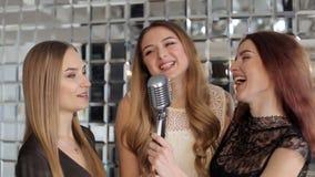 Piękne dziewczyny śpiewa w retro mikrofon przy przyjęciem zbiory