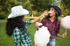 Piękne dziewczyny je bawełnianego cukierek w kowbojskich kapeluszach Obraz Stock