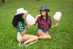 Piękne dziewczyny je bawełnianego cukierek w kowbojskich kapeluszach Zdjęcia Stock