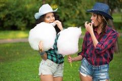 Piękne dziewczyny je bawełnianego cukierek w kowbojskich kapeluszach Zdjęcie Stock