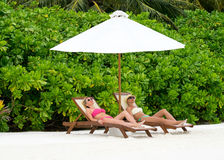 Piękne dziewczyny relaksuje na plażowym krześle blisko Zdjęcie Royalty Free