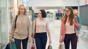 Piękne dziewczyny są gawędzić chodzić wzdłuż centrum handlowego z papierowymi torbami przy weekendem i uśmiechać się - wnętrze zbiory