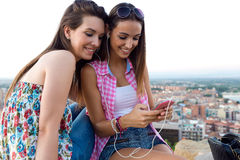 Piękne dziewczyny siedzi na słuchaniu i dachu muzyka przy su Fotografia Royalty Free