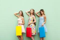 Piękne dziewczyny w sukni, stoi przed zielonym tłem Ręki krzyżować pod głową, trzyma jej kolorowe torby, relaksowali aft Fotografia Stock