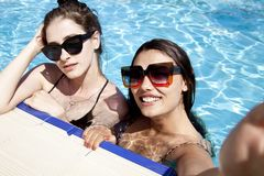 Piękne dziewczyny w swimsuits ma zabawę w basenie poj?cia t?a ramy piasek seashells lato obraz stock