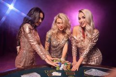 Piękne dziewczyny z doskonalić fryzury i jaskrawy makijaż pozują stać przy uprawia hazard stołem Kasyno, grzebak zdjęcia stock