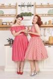 Piękne eleganckie retro kobiety stoi w ich ono uśmiecha się i kuchni obraz stock