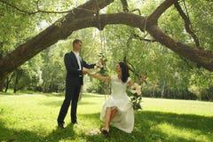 Piękne huśtawki zawieszają w parku na drzewie panna młoda siedzi na huśtawce i trzyma nowożena ` s rękę zdjęcie royalty free