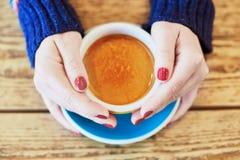 Piękne kobiet ręki z czerwonym manicure'em i filiżanką świeża gorąca kawa na drewnianym stole Zdjęcie Royalty Free