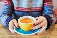 Piękne kobiet ręki z czerwonym manicure'em i filiżanką świeża gorąca kawa na drewnianym stole Obrazy Stock
