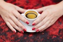 Piękne kobiet ręki z czerwonym manicure'em i filiżanką świeża kawa Fotografia Royalty Free
