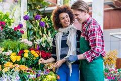 Piękne kobiety kupienia frezje przy rada pomocniczo sprzedawca obraz stock