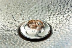 Piękne luksusowe ślubne rinBeautiful luksusowe obrączki ślubne na noni kroplach woda abstrakcjonistyczny tło Obrazy Royalty Free