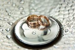 Piękne luksusowe ślubne rinBeautiful luksusowe obrączki ślubne na noni kroplach woda abstrakcjonistyczny tło Fotografia Royalty Free