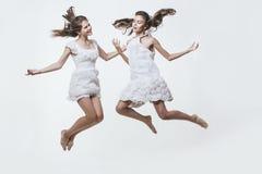 Piękne młode dziewczyny w białych sukniach skaczą wysoko i buntowniczo fotografia stock