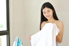 Piękne młode kobiety odprasowywa koszula Zdjęcie Royalty Free