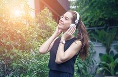 Piękne młode kobiety w przypadkowej sukni, słuchają muzyka, w parkach Zdjęcia Royalty Free