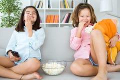 Piękne młode siostry je popkorny w domu obraz stock
