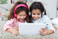 Piękne młode siostry słucha muzyka z cyfrową pastylką a zdjęcie stock