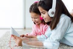 Piękne młode siostry słucha muzyka z cyfrową pastylką a obraz royalty free