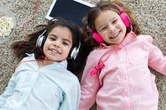 Piękne młode siostry słucha muzyka z cyfrową pastylką a zdjęcia royalty free