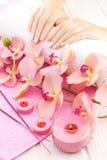 Piękne menchie robią manikiur z orchideą, świeczką i ręcznikiem na białym drewnianym stole, Zdjęcie Royalty Free