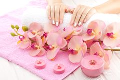 Piękne menchie robią manikiur z orchideą, świeczką i ręcznikiem na białym drewnianym stole, Obrazy Royalty Free