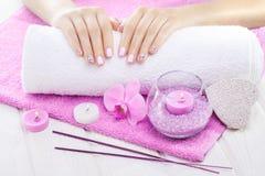 Piękne menchie robią manikiur z orchideą, świeczką i ręcznikiem na białym drewnianym stole, Fotografia Royalty Free