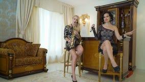 Piękne muzyk brunetki i blondynki młode kobiety są śpiewackim piosenką, bawić się saksofon Seksowne dziewczyny w złotym czerni zdjęcie wideo